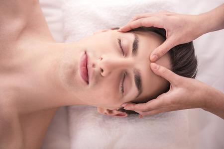 Masaje de cara. Primer plano de un joven macho Conseguir Tratamiento de spa.