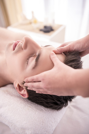 Face Massage. Close-up of a Young Male Getting Spa Treatment. photo