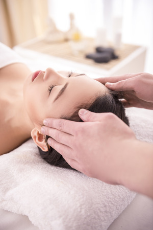 Face Massage. Close-up of a Young Female Getting Spa Treatment. photo