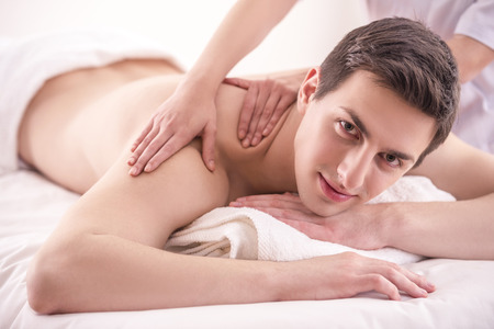masseur: Close-up. Female masseur doing massage on male in the spa salon.