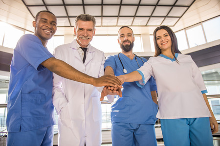 physiotherapists: Smiling group of doctors. Teamwork.  In hospital. Looking at camera. Stock Photo