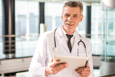hospital corridor: Senior doctor using his tablet in hospital. Stock Photo