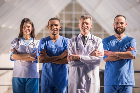 uniformes: Grupo de m�dicos de pie con los brazos cruzados en el hospital.