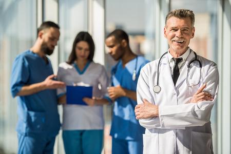 세로 교차 한 팔 함께 서 성숙한 남성 의사 웃 고. 배경 의사가 말하기.