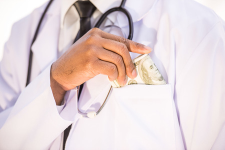 doctor putting money: Close-up. Corruption. Doctor putting money into his pocket. Medicine concept. Stock Photo