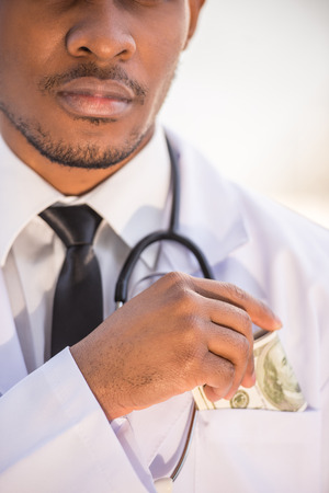 putting money in pocket: Close-up. Corruption. Doctor putting money into his pocket. Medicine concept. Stock Photo