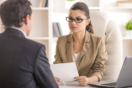 candidate: Businesswoman interviewing male candidate for job in office.