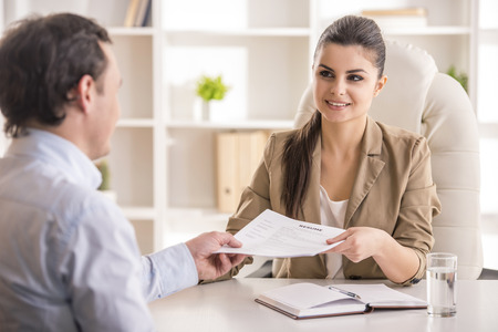 candidates: Businesswoman interviewing male candidate for job in office.