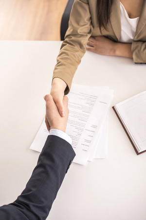 Close-up. Top view. Male candidate shaking hands with businesswoman at desk in office
