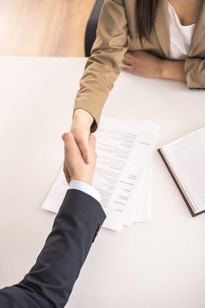 Detailopname. Bovenaanzicht. Mannelijke kandidaat het schudden handen met onderneemster bij bureau in bureau
