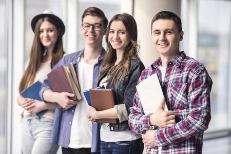 jovenes estudiantes: Grupo de estudiantes jovenes felices en una universidad.