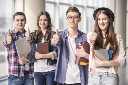 Group of happy young students showing thumbs up in a college. photo
