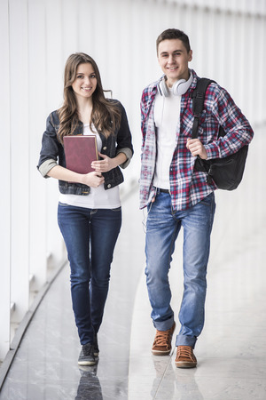 student in library: Full length. Two young atractive studens in college. Stock Photo