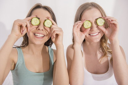 pajama party: Close-up. Pajama party. Two young smiling girlfriend putting on eyes cucumber. Stock Photo