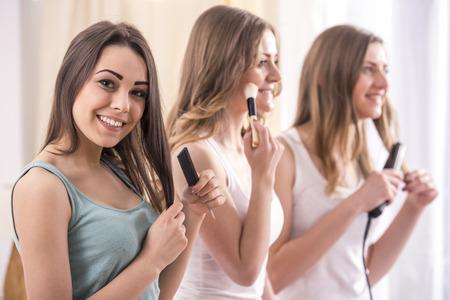 pijamada: Fiesta de pijamas. Muchachas de la belleza j�venes haciendo maquillaje y pelos.