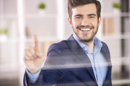 Young handsome businessman pressing on glass screen in office. photo