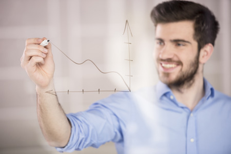 students studying: Young handsome businessman drawing a graph on glass screen in office.