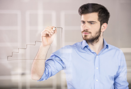 Young handsome businessman drawing on glass screen in office. photo