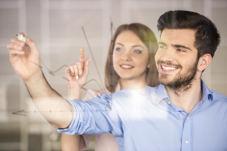 handsome man: Young businessman and businesswoman  drawing a graph on glass screen in office.