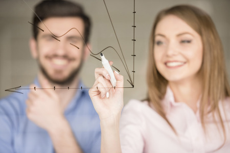modern businessman: Young businessman and businesswoman  drawing a graph on glass screen in office.