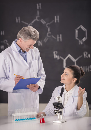 Senior chemistry professor and his assistant working  in  laboratory.