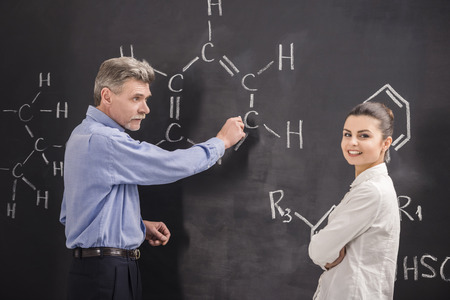 lecturing hall: Professor of chemistry writes on the blackboard formula together with his student.