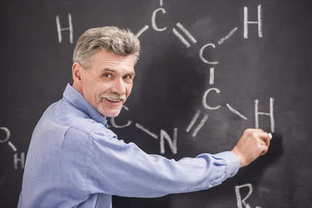 lecturing hall: Professor of chemistry writes on the blackboard formula in University.