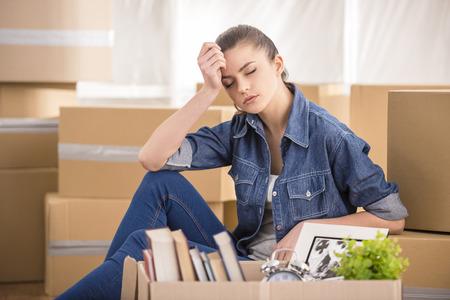 Die junge glückliche Frau sitzt in einem Raum in der Nähe von Boxen. Bewegen, Kauf von neuen Wohnung.