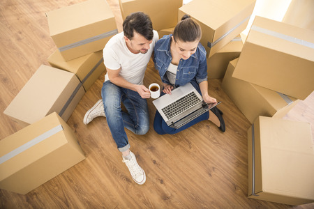 The young happy couple searching for apartments with laptop. Moving, purchase of new habitation. Stock Photo