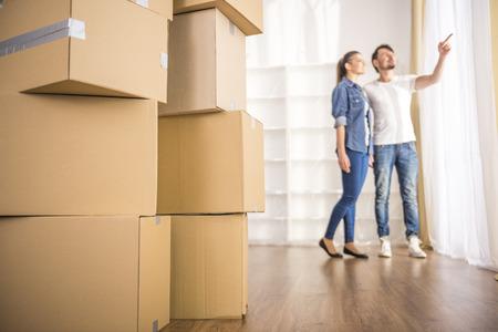 De jonge gelukkige paar kijken rond hun nieuwe appartement. Bewegende, de aankoop van de nieuwe woning.