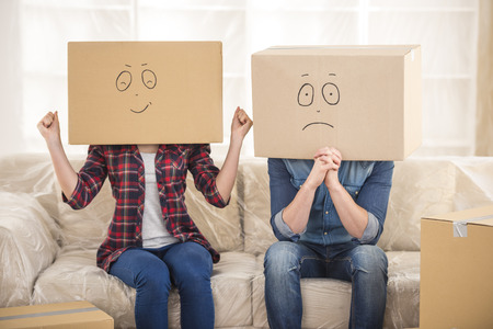 Couple with cardboard boxes on their heads with smiley face are sitting on floor after the moving house.