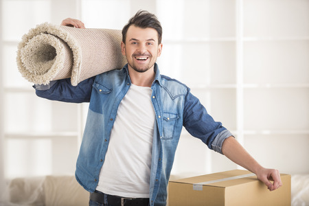 carpet: The young happy man keeping carpet. Moving, purchase of new habitation. Stock Photo