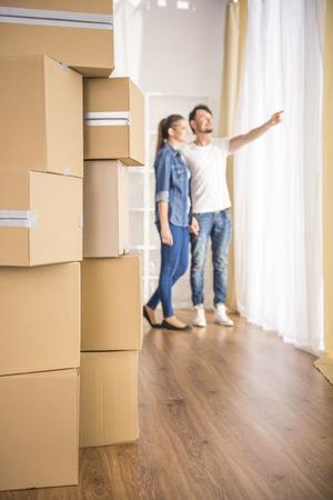 若い幸せなカップルは、彼らの新しいアパートの周り探しています。新しい居住地の移動、購入。