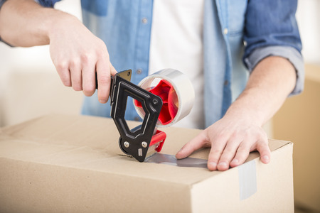 people moving: Close-up. Man packing boxes. Moving, purchase of new habitation. Stock Photo