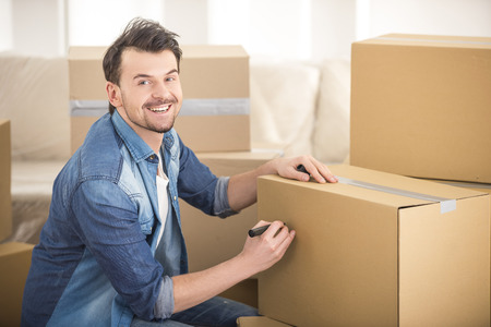 moving box: The young happy man signing box. Moving, purchase of new habitation.