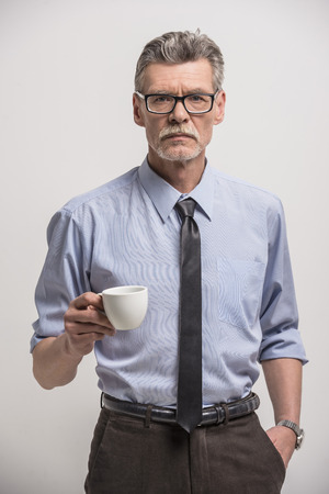 Serious senior male in glasses with cup of coffee on grey background.
