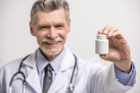 doctor holding pills: Senior male doctor holding pills on grey background. Focus on pills.