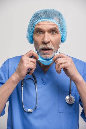 surgeon mask: Senior male doctor in surgeon mask and medical cap.