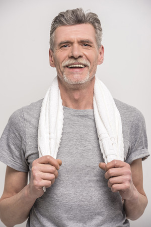 fitness hombres: Hombre mayor sonriente en camiseta en la toalla del cuello sobre fondo gris. Foto de archivo