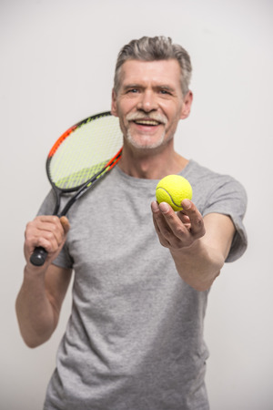 Senior male trainer with tennis racket and tennis. photo