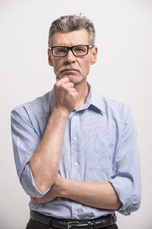 1 mature man: Portrait of senior man glasses on the grey background.