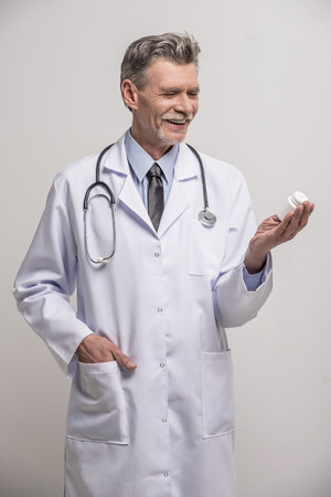 doctor holding pills: Senior male doctor holding pills on grey background.