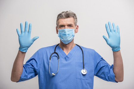 surgeon mask: Senior male doctor in surgeon mask and rubber gloves. Stock Photo