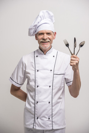 snoop: Senior male chief cook in uniform holding fork, snoop and knife a  on grey background.