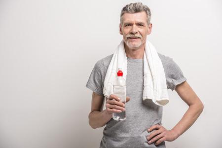 Lachende senior man in T-shirt op de hals handdoek met een fles water op een grijze achtergrond. Stockfoto