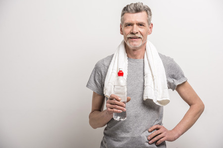 Exercising: Smiling senior man in T-shirt on neck towel with bottle water on grey background.