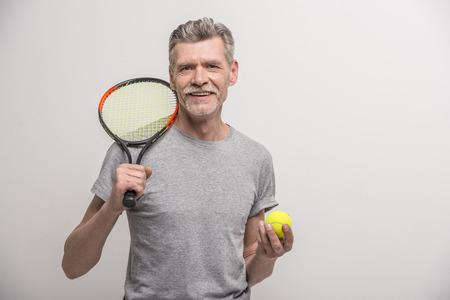 raqueta de tenis: Entrenador varón mayor con raqueta de tenis y tenis.