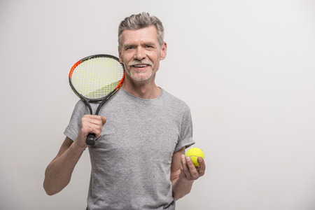 Senior male trainer with tennis racket and tennis.