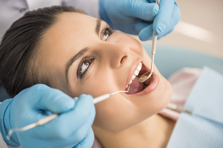 oral care: Dentist examining a patients teeth in the dentist. Stock Photo