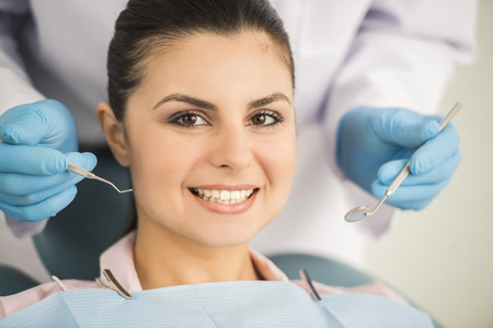 visit: Dentist examining a patients teeth in the dentist. Stock Photo